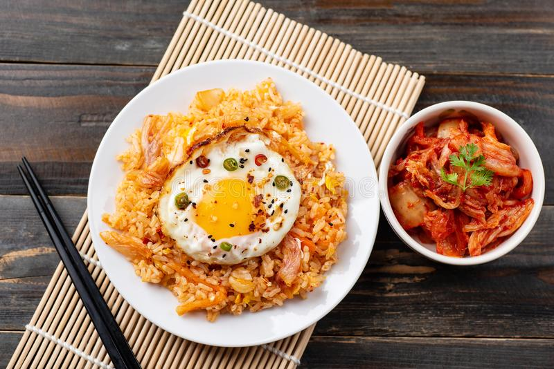 Kimchi fried rice with fried egg on top. And fresh kimchi cabbage in a bowl, top view, Korean food stock photos