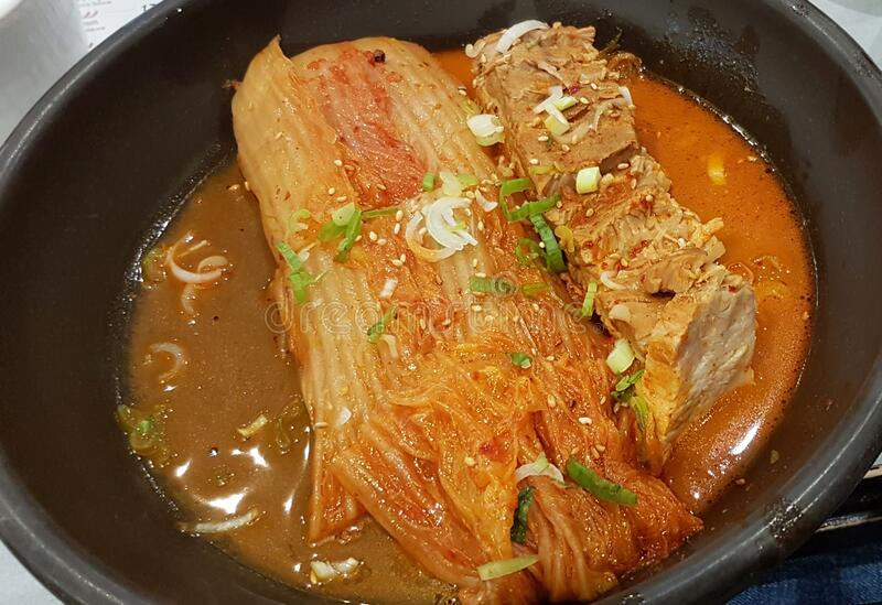 Kimchi Pork Tenderloin. Sour and Spicy Korean Kimchi amd slow cooked pork tenderloin with green onion and sesame in a plate stock images