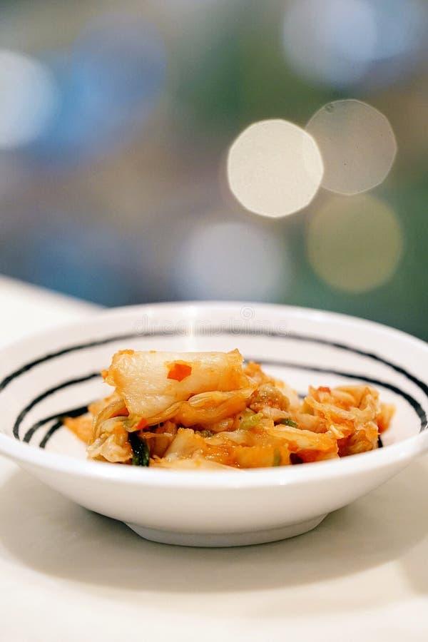 Kimchi, quello è un piatto laterale coreano, è in piccola ciotola bianca con il fondo vago del bokeh delle luci fotografia stock libera da diritti