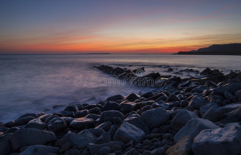 Kimmeridge Bay with wet rocks and sunset royalty free stock image