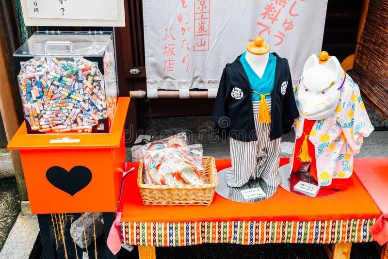 Kimono tradizionale giapponese per i bambini e la scatola di Omikuji alla vecchia via di Higashiyama a Kyoto, Giappone immagine stock libera da diritti