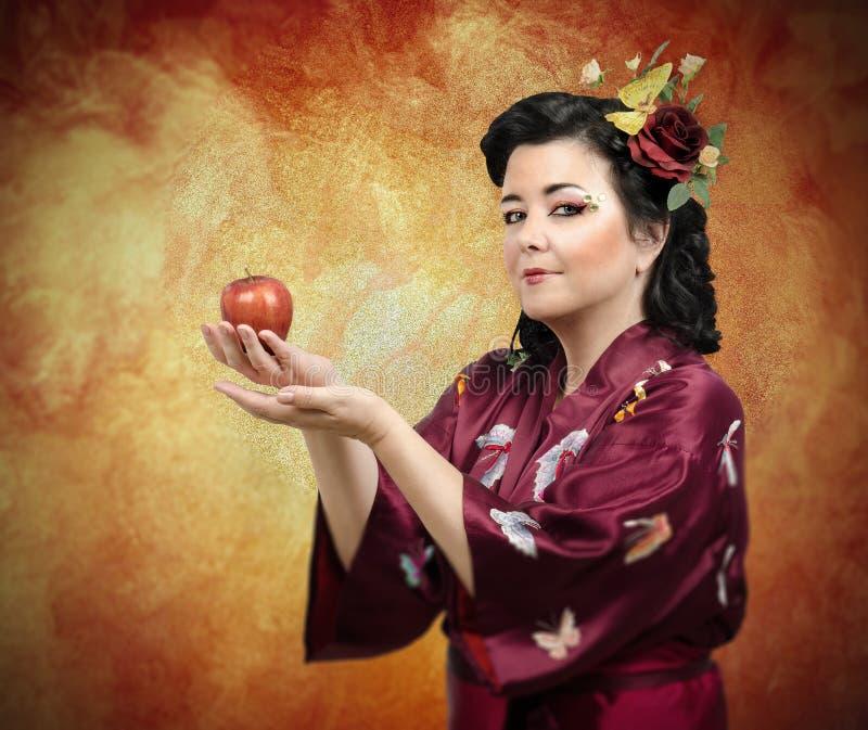 Kimonovrouw die haar wapens met appel uitbreiden stock foto's