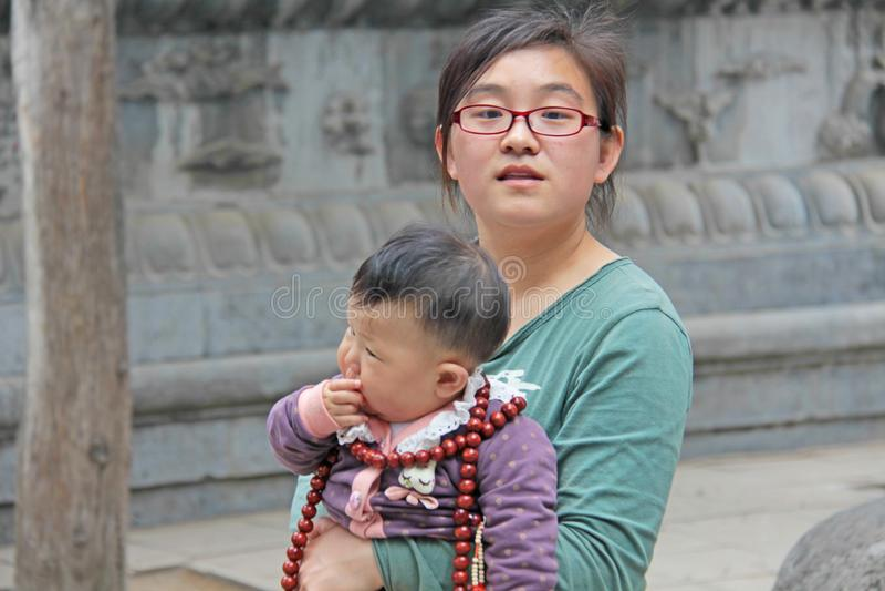 Kina Shaolin - April 11, 2012 Kinesisk ung moderflicka med ett barn i hennes armar på den Shaolin kloster, Kina fotografering för bildbyråer
