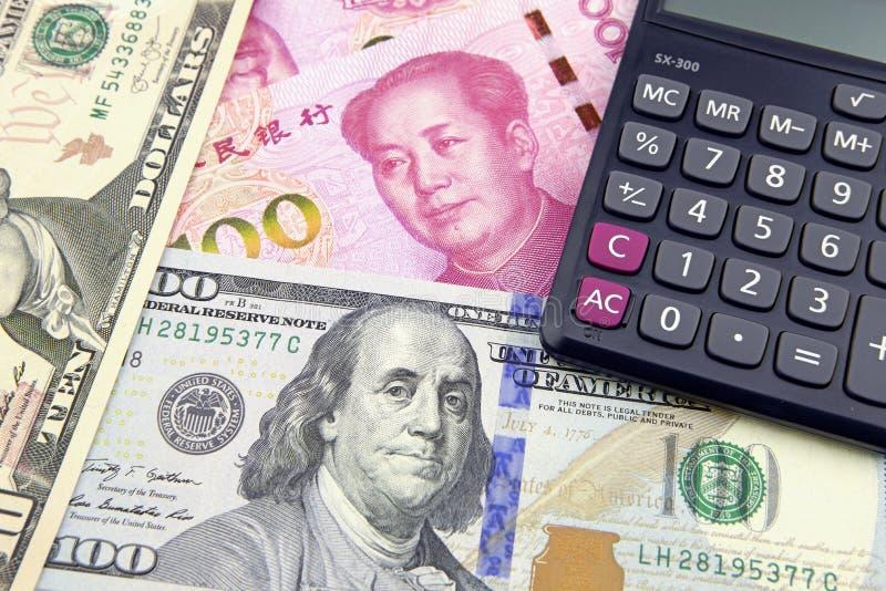 Kina Yuan och US dollar med en räknemaskin royaltyfria foton