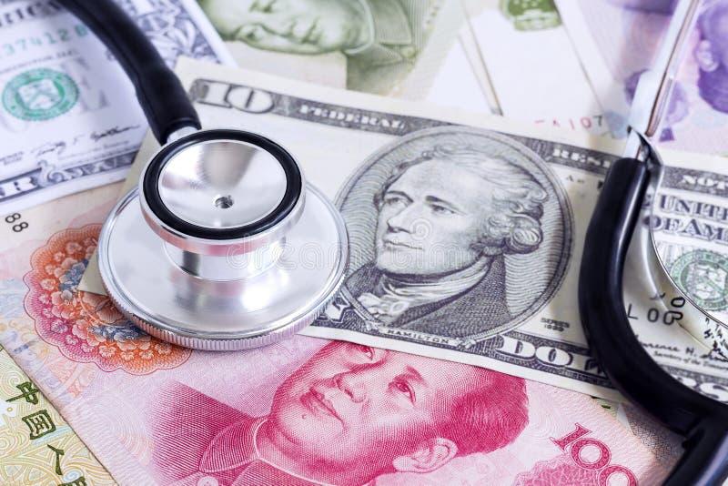 Kina yuan, oss dollarsedel och stetoskop på en hög av byrackan arkivfoton
