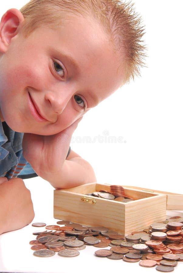 Kind über Geldkasten stockbild