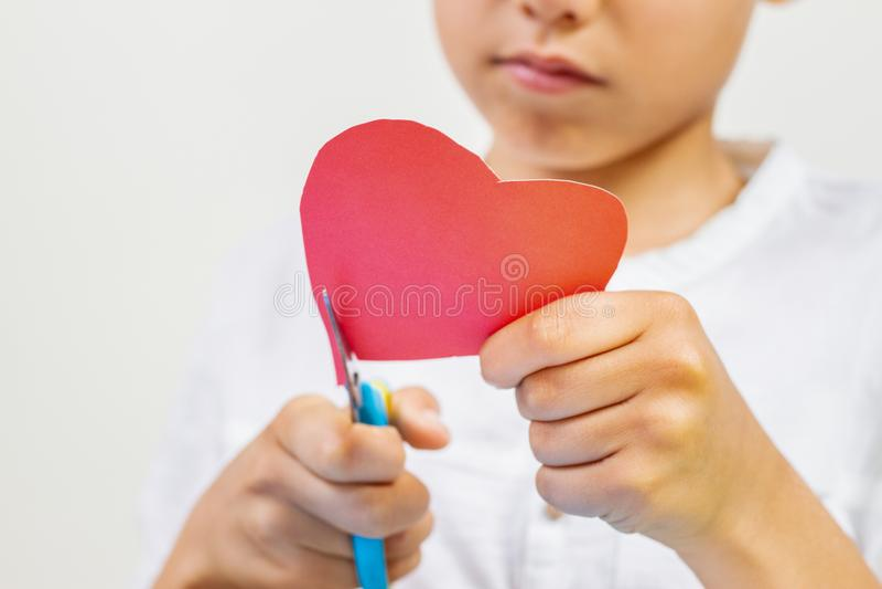 Kind übergibt den Schnitt des roten Papierherzens mit Scheren lizenzfreies stockbild