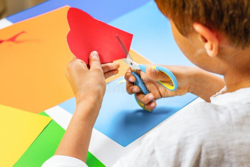 Kind übergibt den Schnitt des roten Papierherzens mit Scheren am Tisch stockfotos