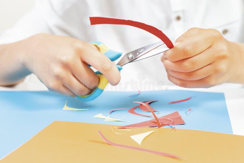 Kind übergibt farbiges Papier des Ausschnitts mit Scheren am Tisch stockfoto
