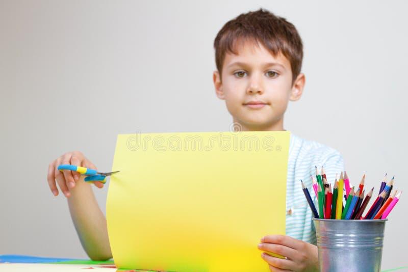 Kind übergibt farbiges Papier des Ausschnitts mit Scheren am Tisch stockfotos