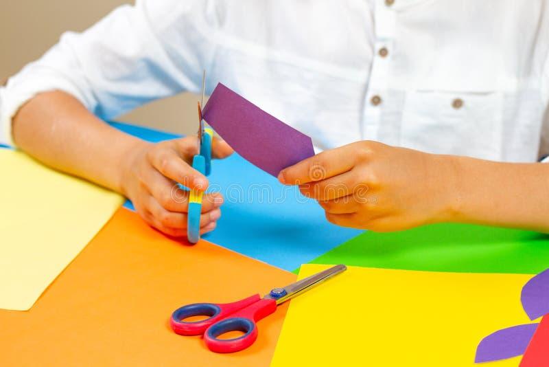 Kind übergibt farbiges Papier des Ausschnitts mit Scheren am Tisch lizenzfreie stockfotos