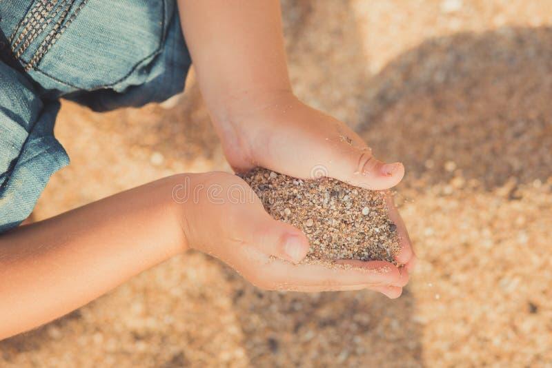 Kind übergibt Nahaufnahme von der Hand gießt Sandlebensstilkontakt-Stammbaumgeschlecht stockbild