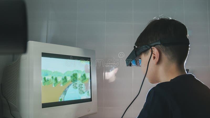 Kind überprüft Vision mit den Stereovideogläsern der virtuellen Realität - Augenheilkundeklinik stockfotografie