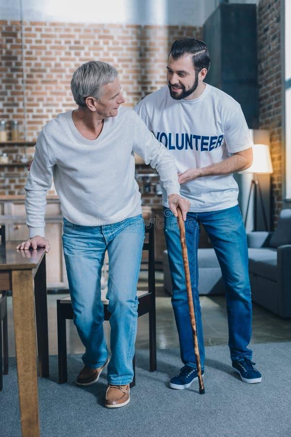 Kind alert man helping an aged man royalty free stock image