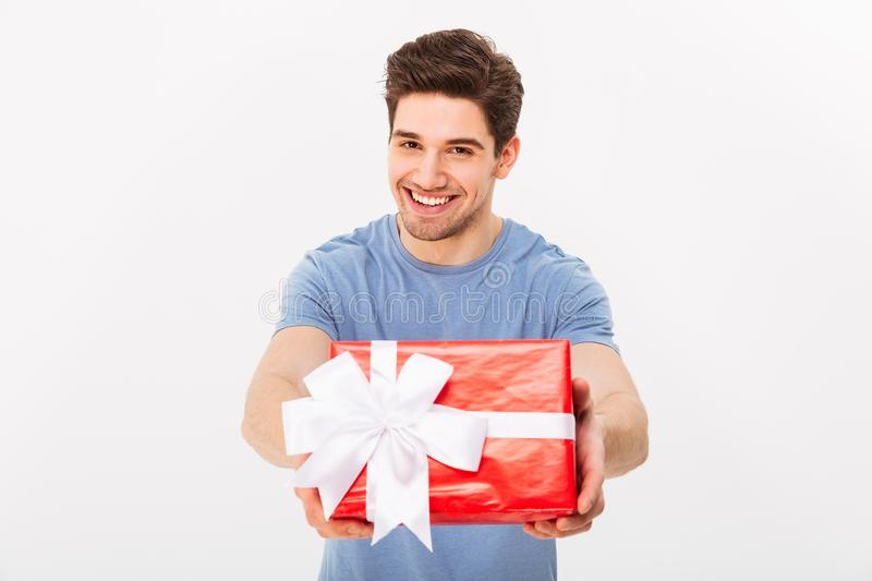 Kind attractive man with beautiful smile giving birthday present. On camera isolated over white wall stock photo