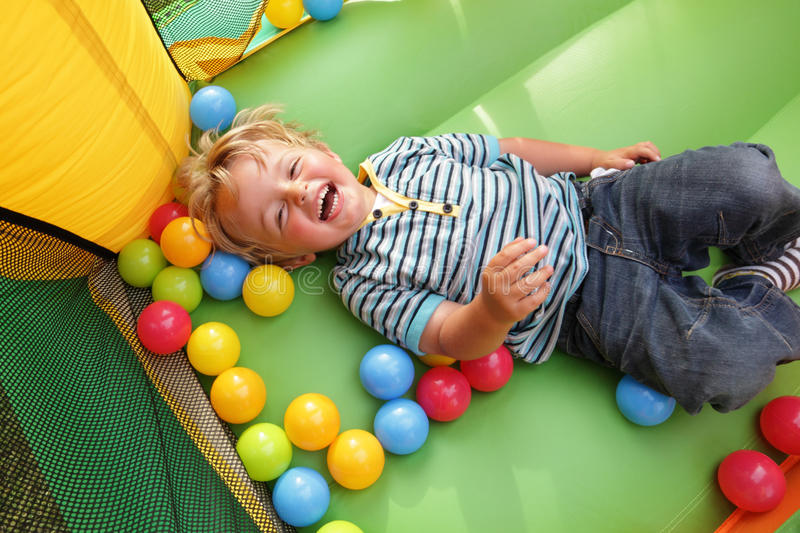 Kind auf aufblasbarem federnd Schloss lizenzfreies stockfoto