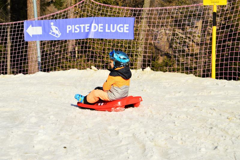 Kind auf bobsleight in der Schweiz stockbild