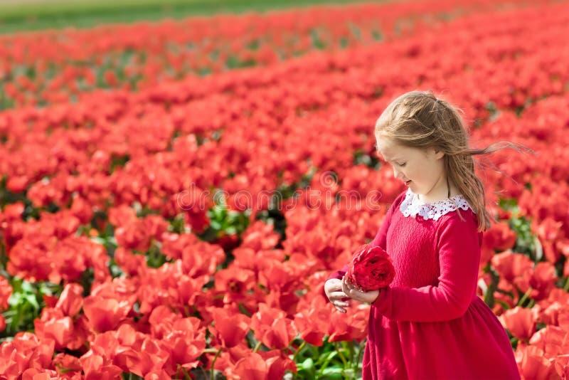 Kind auf dem roten Blumengebiet Mohnblumen- und Tulpengarten lizenzfreies stockfoto