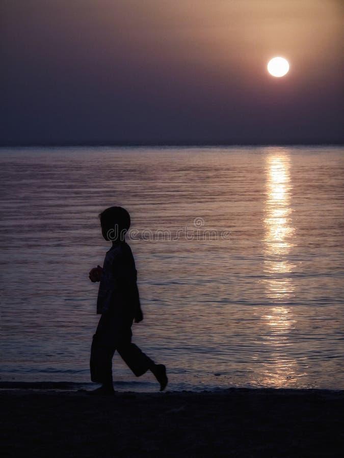 Kind auf dem Strand, der am Sonnenunterganghaus läuft lizenzfreie stockfotografie
