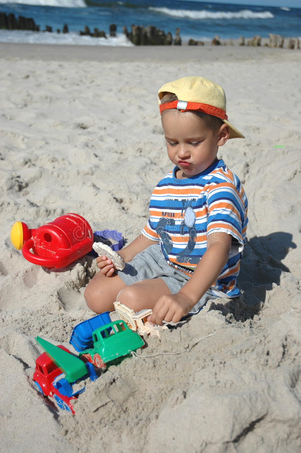 Kind auf dem Strand mit Plätzchen lizenzfreie stockbilder