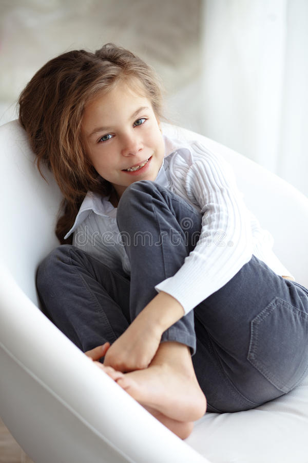 Kind auf einem Stuhl stockbild
