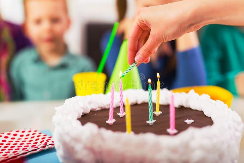 Kind auf Geburtstagsfeier bereitete Schlagkerzen auf Kuchen, selektiver Fokus vor lizenzfreie stockfotos