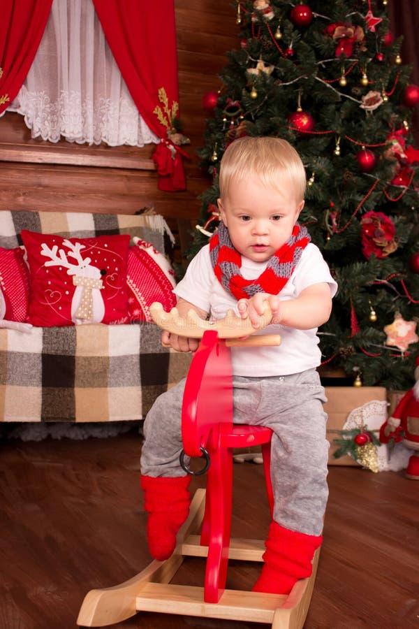 Kind auf hölzernen Rotwild in der Weihnachtsdekoration stockfotografie
