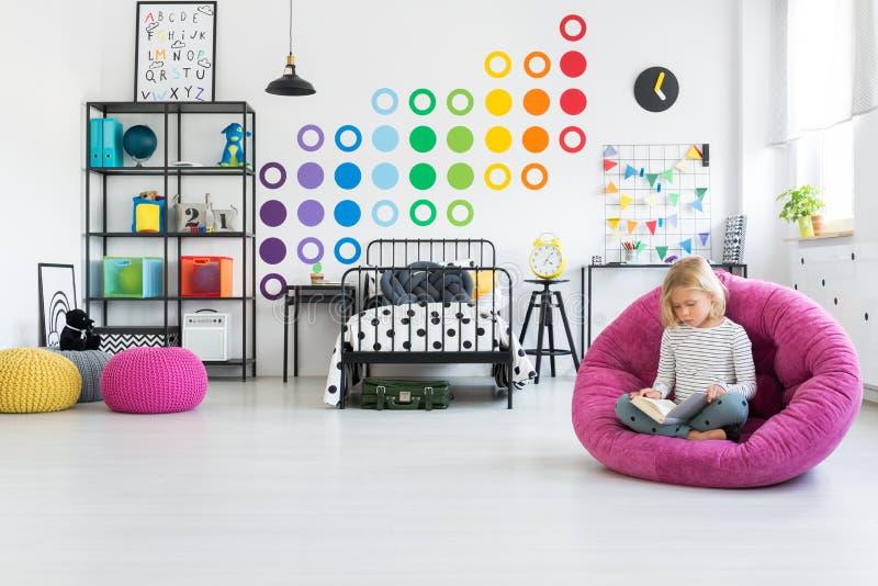 Kind auf Puff im Schlafzimmer lizenzfreie stockfotos