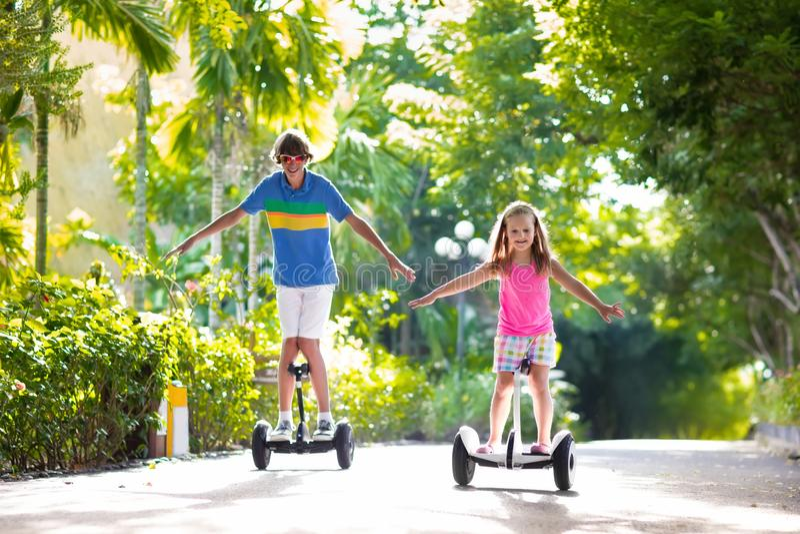 Kind auf Schwebeflugbrett Kinder, die Roller reiten stockbilder