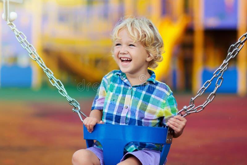Kind auf Spielplatz Schwingen Kinder spielen im Freien stockfotografie