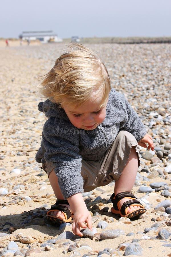 Kind auf Strand mit Kieseln stockbild