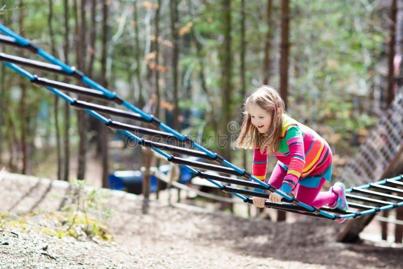 Kind in avonturenpark Jonge geitjes die kabelsleep beklimmen royalty-vrije stock foto