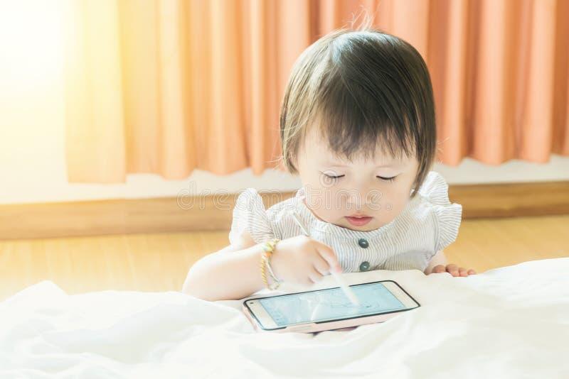 Kind, Baby auf einem weißen Bett, zeichnendes A B C unter Verwendung des intelligenten Gerätstiftes am intelligenten Telefon mit  lizenzfreies stockbild