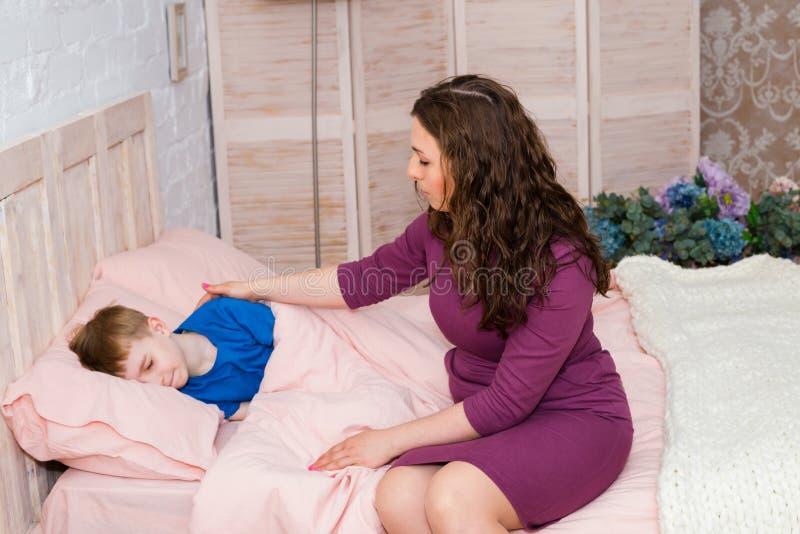 Kind in bed thuis met moeder Jongen in bedslaap stock afbeeldingen