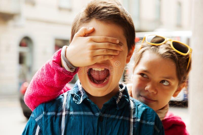 Kind bedeckt Augen ihres Bruders, Porträt stockfotografie