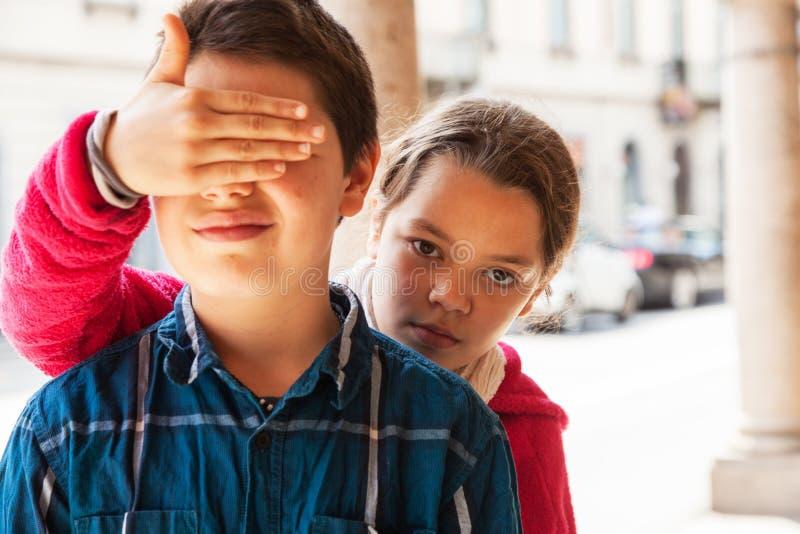 Kind bedeckt Augen ihres Bruders, Porträt lizenzfreies stockbild