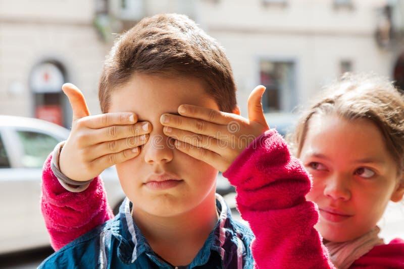 Kind bedeckt Augen ihres Bruders, Porträt lizenzfreies stockfoto