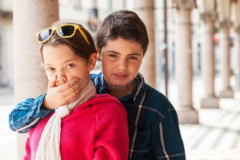 Kind bedeckt ihren Mund ihrer Schwester, Porträt lizenzfreie stockfotografie