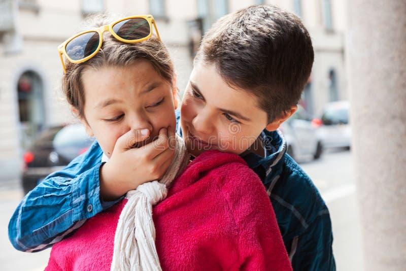 Kind bedeckt Mund seiner Schwester, Porträt lizenzfreie stockfotografie