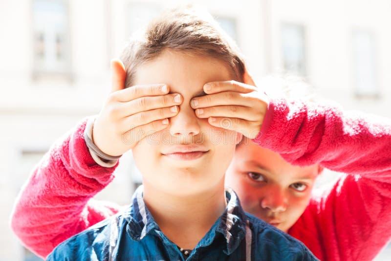 Kind bedeckt seine Augen mit seinem Bruder, Porträt lizenzfreie stockfotos