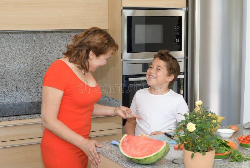 Kind befleckt Hemdwann vorbereitet das Mittagessen mit seiner Mutter und Lachen stockfoto