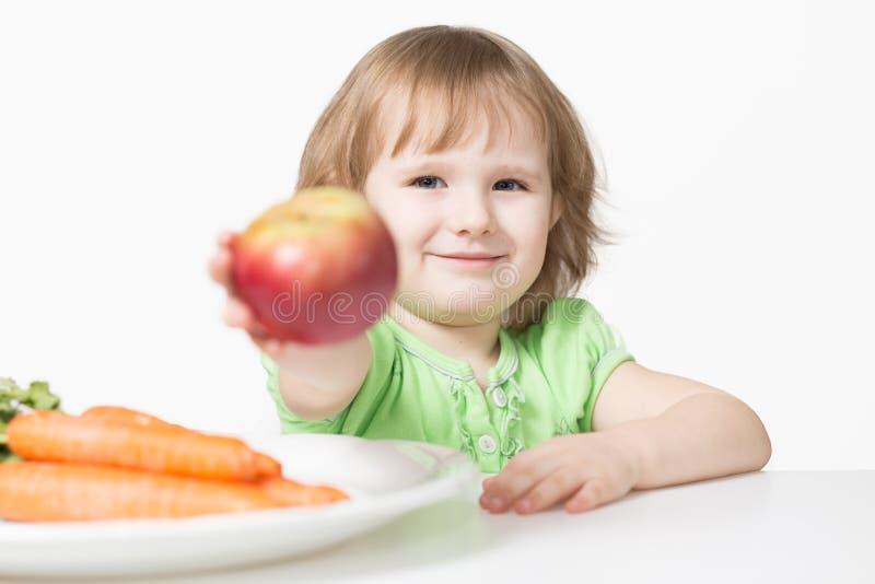 Kind bietet Apfel an stockfotos