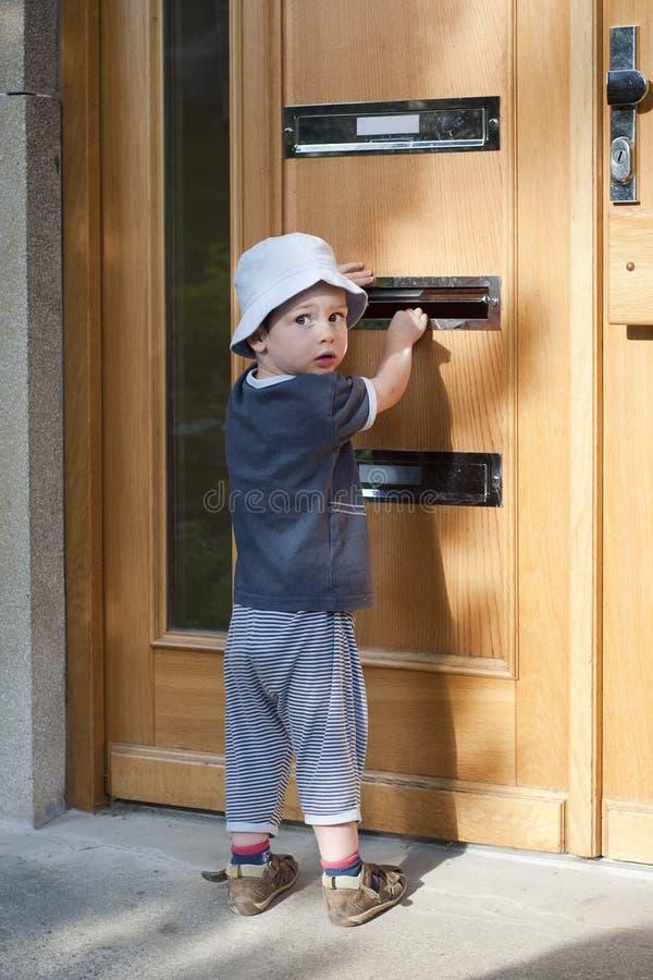 Kind bij deur met brievenbus stock fotografie