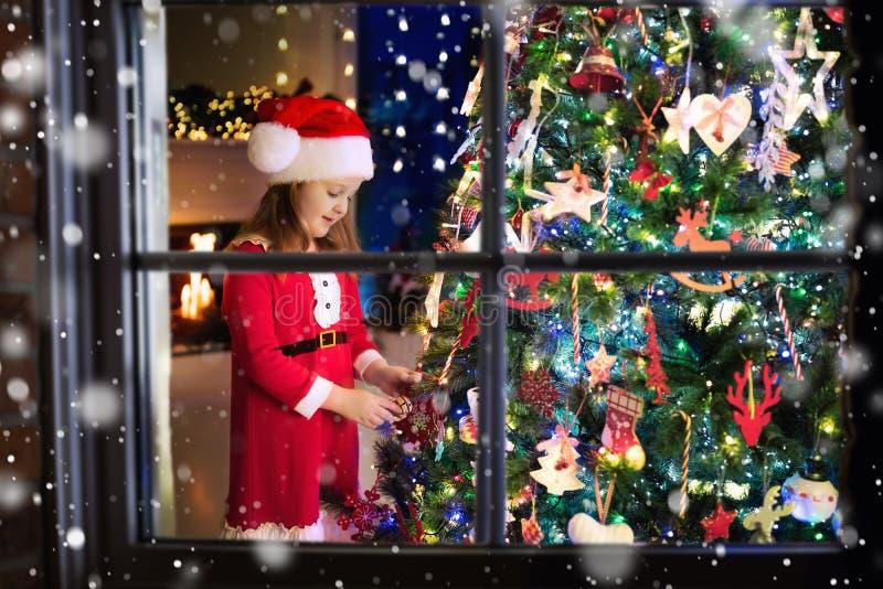 Kind bij Kerstboom Jong geitje bij open haard op Kerstmisvooravond royalty-vrije stock foto's