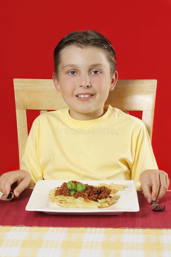 Kind bij lijst met plaat van voedsel stock afbeeldingen