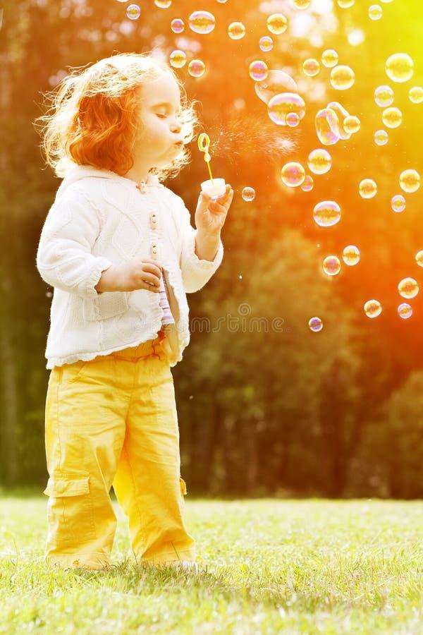 Kind blazen zeepbels Jong geitje blazende bellen op aard bab stock afbeelding