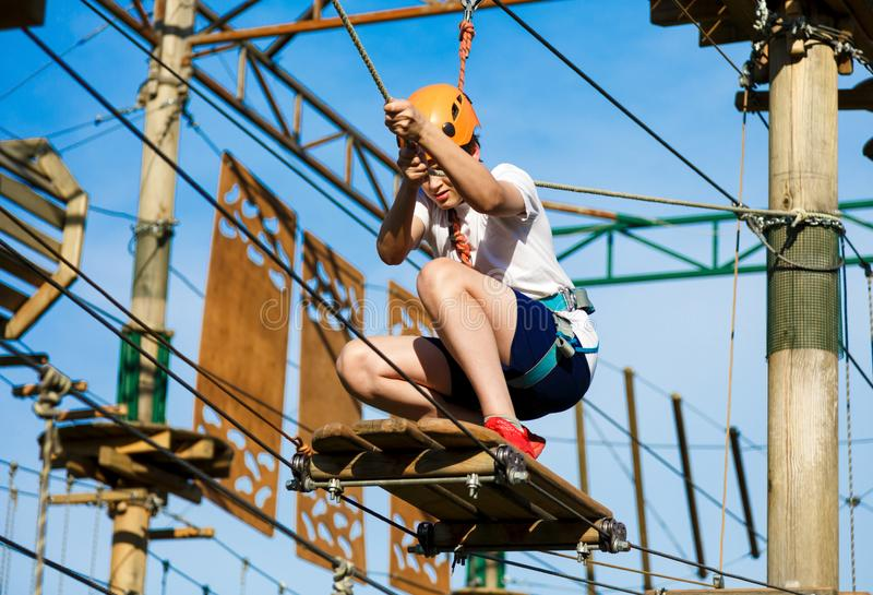 Kind in bosavonturenpark Het jonge geitje in oranje helm en witte t-shirt beklimt op hoge kabelsleep Behendigheidsvaardigheden stock fotografie