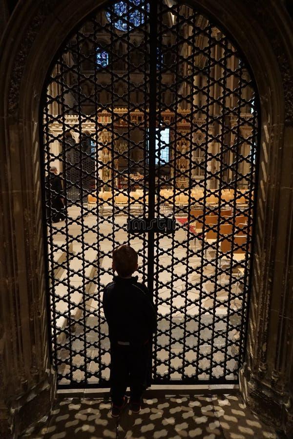 Kind in Canterbury-Kathedrale, die durch die aufwändige Eisen-Tür schaut (Innen) stockbild