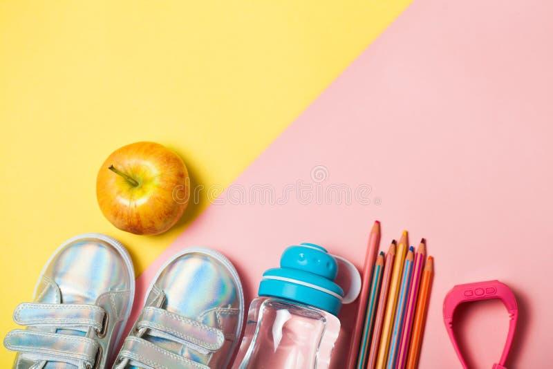 Kind-clothesand Studienmaterial: sneackers, Bleistifte, Flasche Wasser und Elektron gps-Uhren stockfotografie