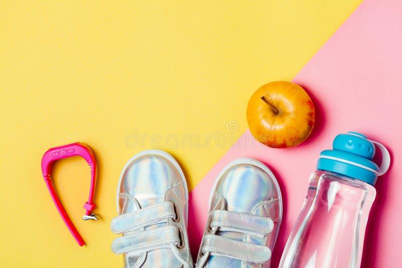 Kind-clothesand Studienmaterial: sneackers, Bleistifte, Flasche Wasser und Elektron gps-Uhren lizenzfreie stockfotografie